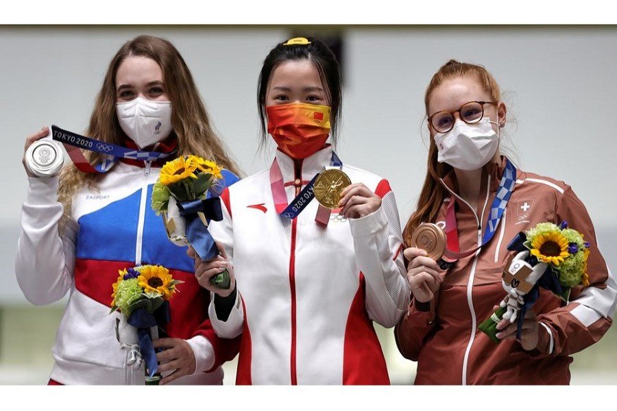 Tokyo 2020 Olympics - Shooting - Women's 10m Air Rifle - Medal Ceremony - Asaka Shooting Range, Tokyo, Japan – July 24, 2021. Gold medallist Yang Qian of China celebrates on the podium with silver medallist, Anastasiia Galashina of the Russian Olympic Committee and bronze medallist, Nina Christen of Switzerland – Reuters/Ann Wang