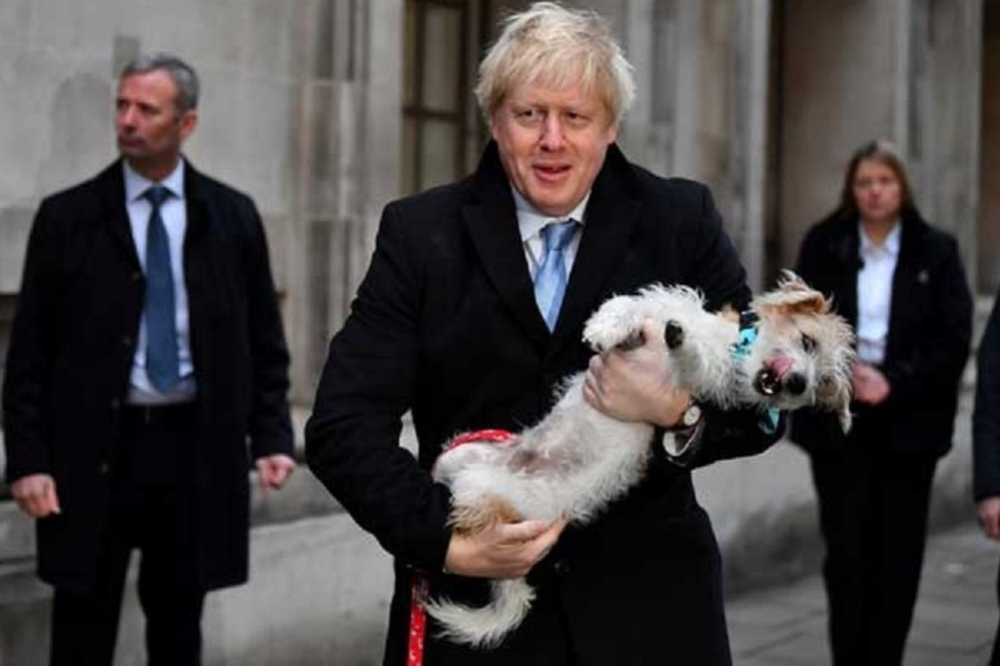 Britain's Prime Minister Boris Johnson holds his dog Dilyn as he leaves a polling station, at the Methodist Central Hall, after voting in the general election in London, Britain, December 12, 2019. REUTERS/Dylan Martinez