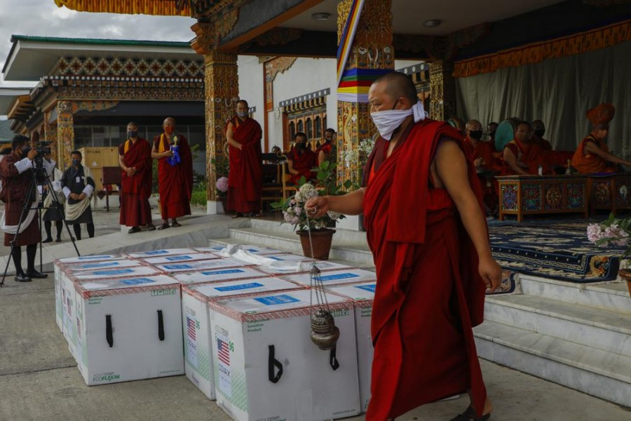 This photograph provided by UNICEF shows monks from Paro's monastic body perform a ritual as 500,000 doses of Moderna COVID-19 vaccine gifted from the United States arrived at Paro International Airport in Bhutan, July 12, 2021. (UNICEF via AP)