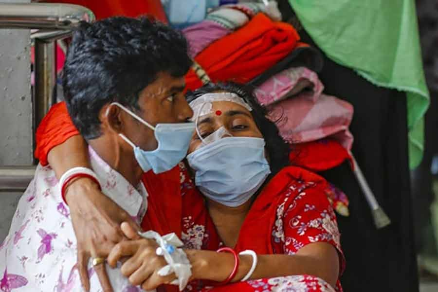 Husband carrying suspected coronavirus patient Shipra, who gave a single name and also has typhoid, into Dhaka Medical College Hospital as they arrive from Bogura recently -bdnews24.com file photo