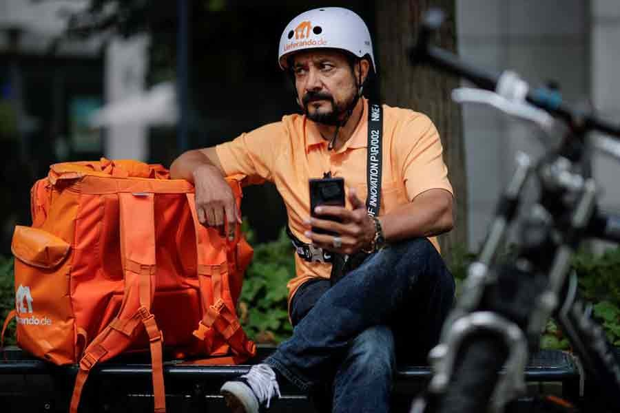 Former Afghan Communication Minister Sayed Sadaat sitting in his orange uniform next to his bike on Wednesday as he works for a food delivery service in Leipzig of Germany -Reuters Photo