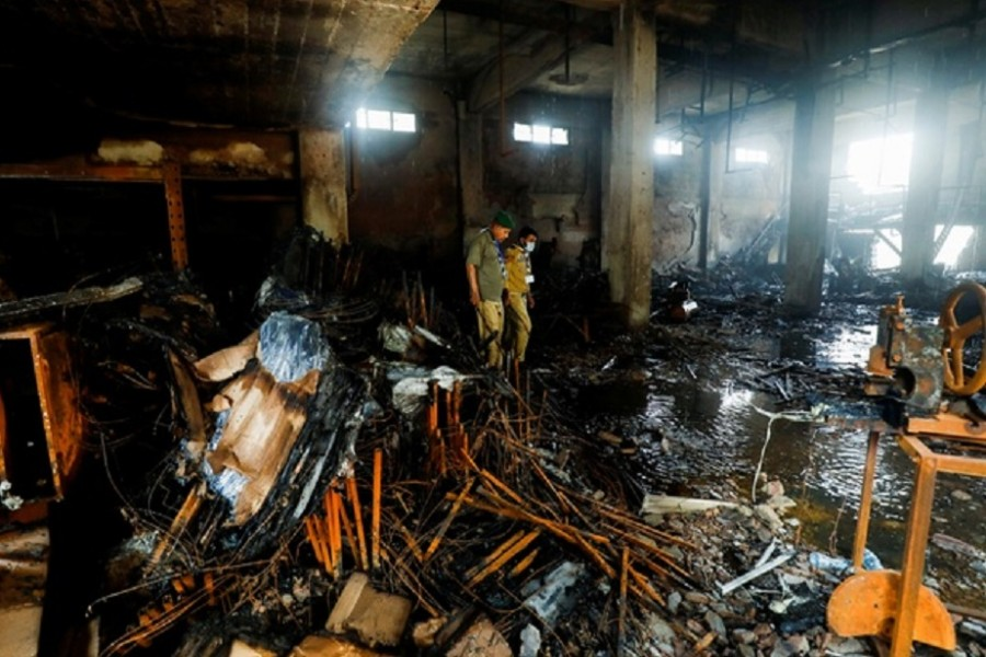 Members of the scout emergency response team, survey amid the burned wreckage, after a fire broke out at a multi-story chemical factory, in Karachi, Pakistan, August 27, 2021. Reuters