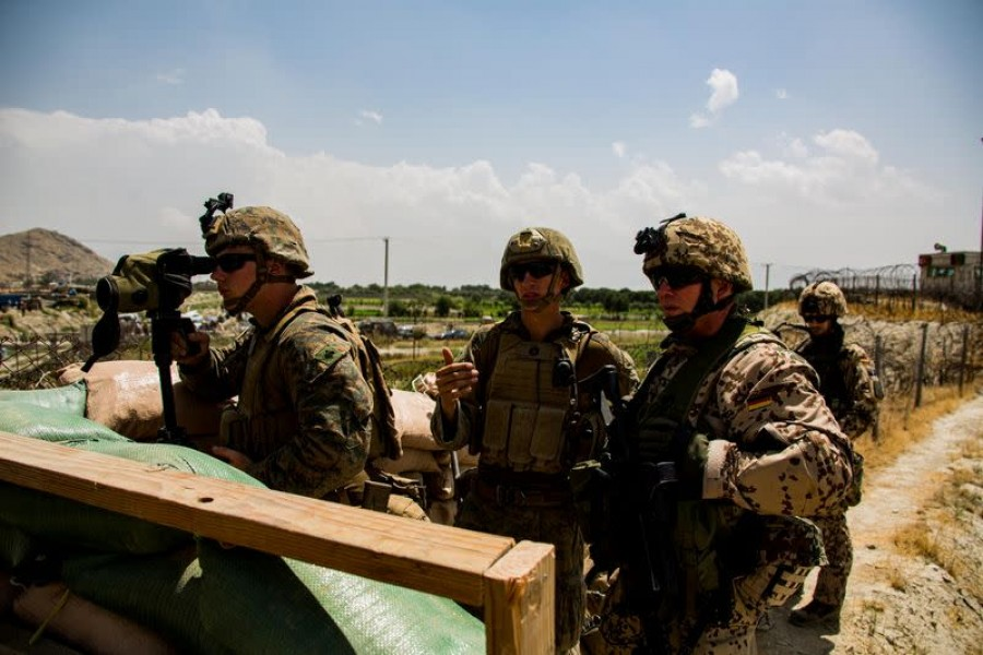 US Marines and German service member watch an entry gate during an evacuation at Hamid Karzai International Airport, Kabul, Afghanistan on August 28, 2021 — US Marine Corps Handout Via Reuters