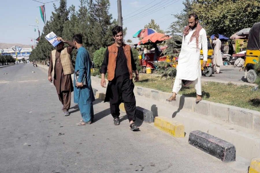 People walk on the street leading to the airport's Abbey gate where a blast occurred two days earlier, in Kabul, Afghanistan August 28, 2021. REUTER/Stringer