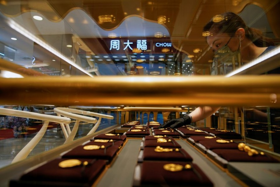 A salesperson poses with Heritage Gold jewellery at jeweller Chow Tai Fook's retail store in Shanghai, China August 18, 2021. Picture taken August 18, 2021. REUTERS/Aly Song