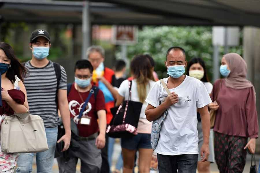 People wearing face masks crossing a road amid the coronavirus disease (COVID-19) outbreak in Singapore on May 14 this year -Reuters file photo