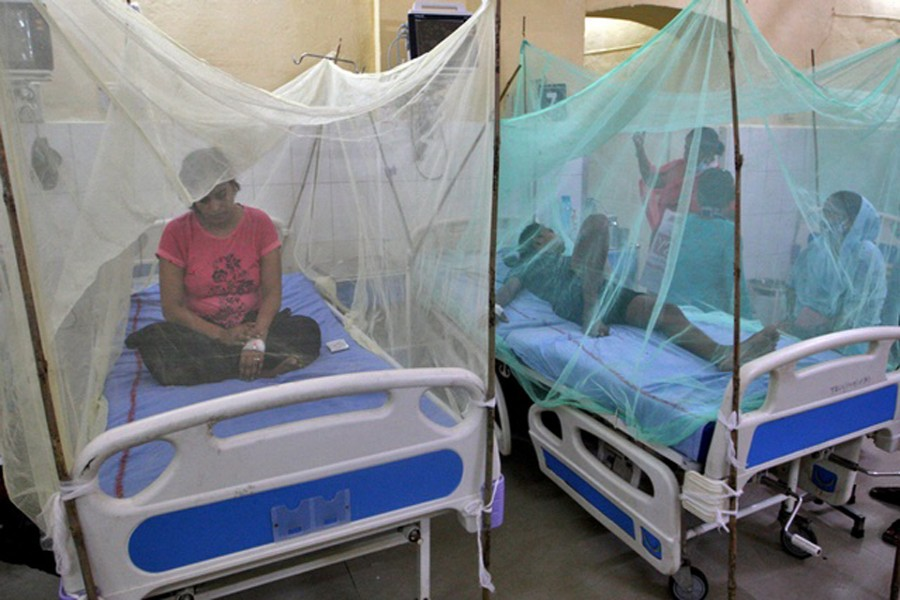 Dengue-infected patients sit under the mosquito nets after being hospitalised at Tej Bahadur Sapru Hospital in Prayagraj, in the northern state of Uttar Pradesh, India, Sept 13, 2021. REUTERS/Jitendra Prakash