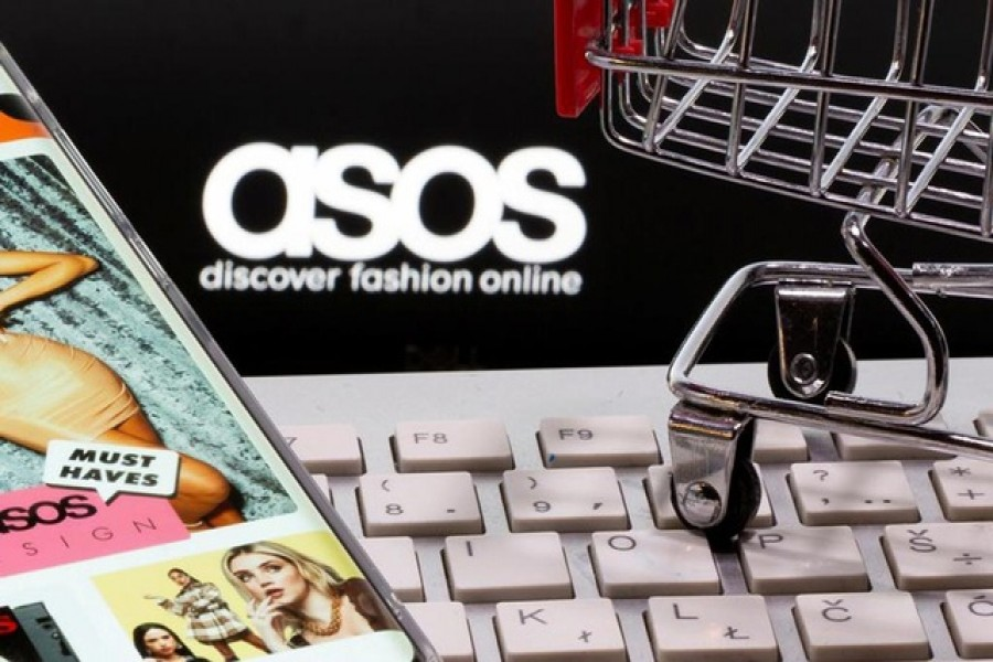 A smartphone with the ASOS app and a keyboard and shopping cart are seen in front of a displayed ASOS logo in this illustration picture taken October 13, 2020. REUTERS/Dado Ruvic