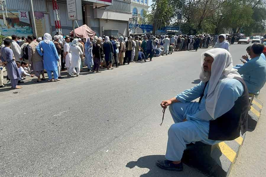 Afghans waiting outside a bank in Kabul in a long queue on September 1 this year to take out their money after Taliban takeover in Afghanistan -Reuters file photo