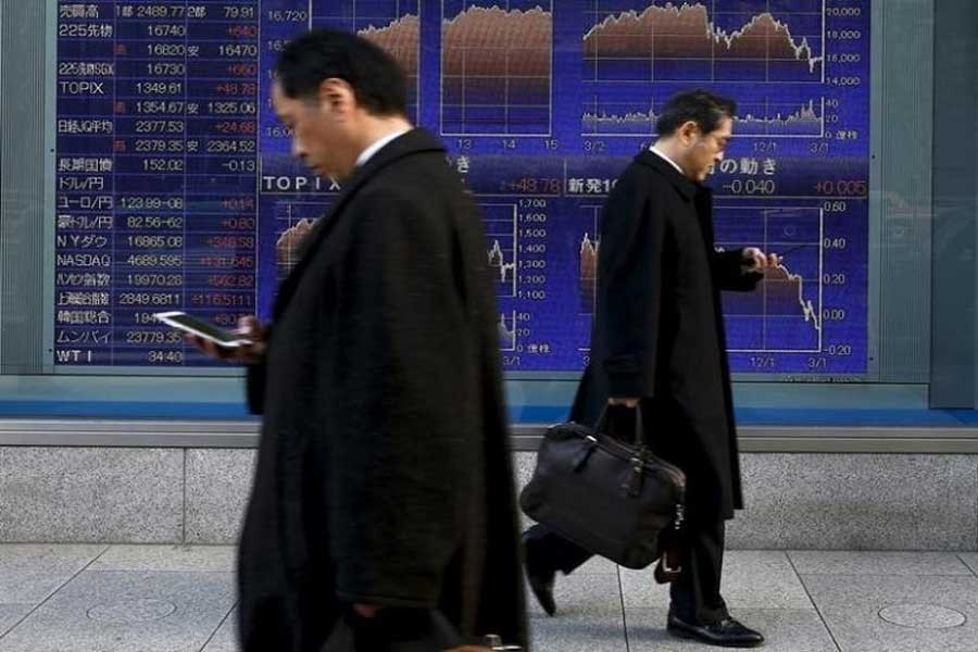 Men walk past an electronic board showing market indices outside a brokerage in Tokyo, Japan, March 2, 2016. Reuters