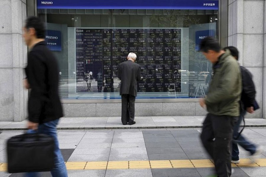 A man looks at a stock quotation board outside a brokerage in Tokyo, Japan, April 18, 2016. Reuters