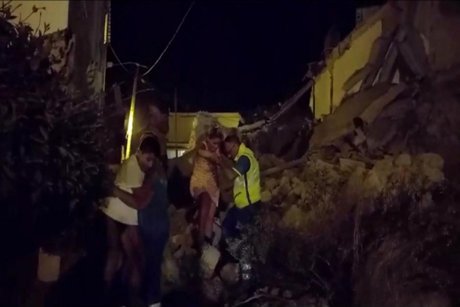 A woman is helped out of debris and rubble after an earthquake hit the island of Ischia, off the coast of Naples, Italy on Monday.
