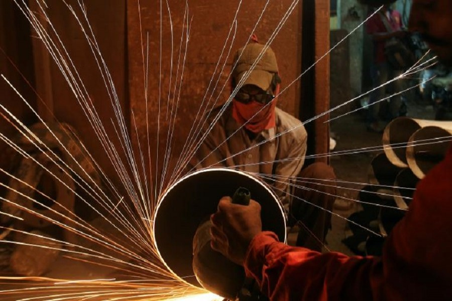 A worker cuts metal inside a workshop manufacturing pipes in Mumbai, India August 11, 2017. Reuters