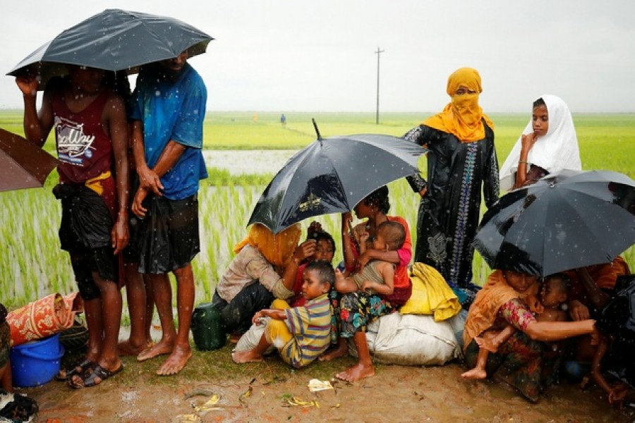 Rohingya refugees with children sit in an open place during heavy rain, as they are held by Border Guard Bangladesh (BGB) after illegally crossing the border, in Teknaf.—Reuters