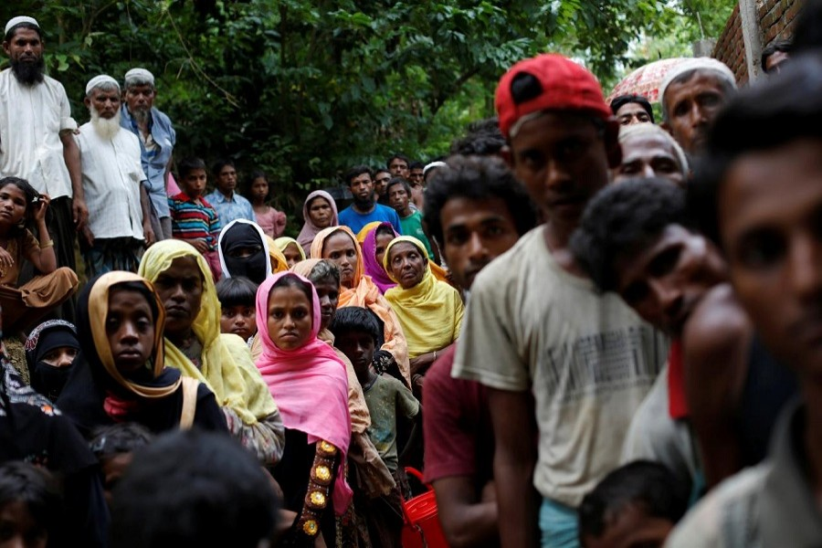 Rohingya refugees wait for food near Kutupalong refugee camp after crossing the Bangladesh-Myanmar border in Ukhia, Bangladesh, September 6, 2017. Reuters