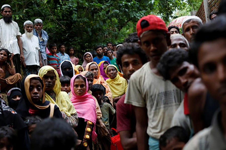 Rohingya refugees wait for food near the Kutupalong refugee camp in Bangladesh on Wednesday last after crossing the Myanmar border. - Reuters photo