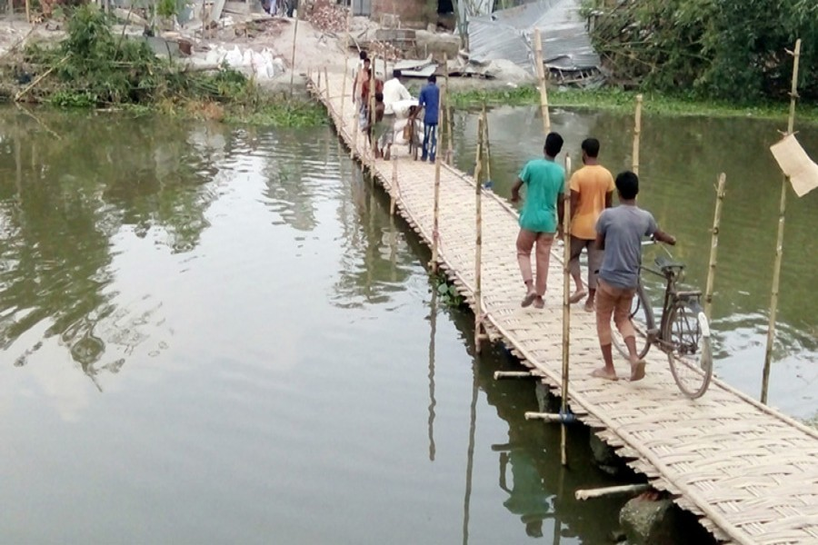 Local people built a bamboo bridge on the broken part of a road in Alemarbazar area under Gangachara upazila of Rangpur. — FE Photo