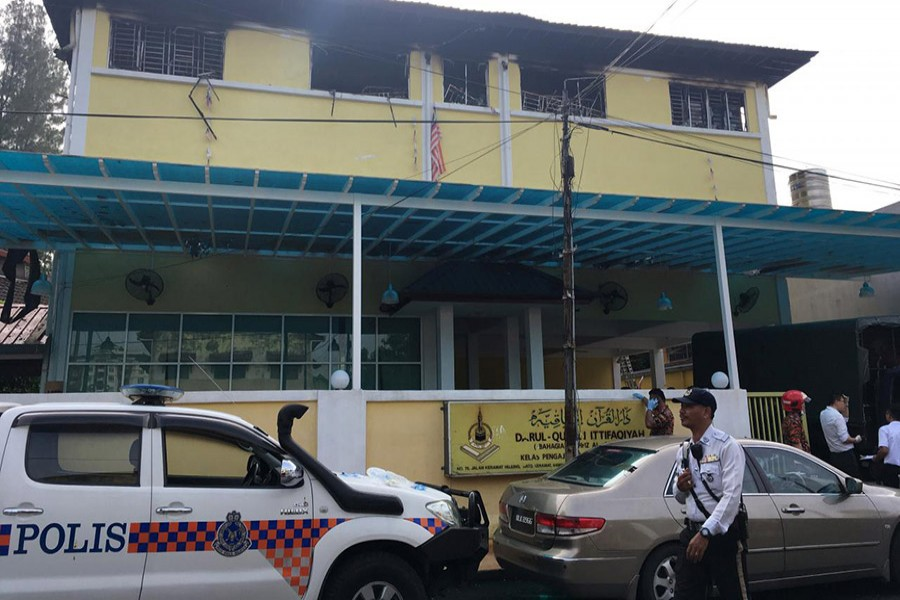 Police and fire department work at the religious school Tahfiz Darul Quran Ittifaqiyah after a fire broke out in Kuala Lumpur, Malaysia early Thursday. - Reuters photo
