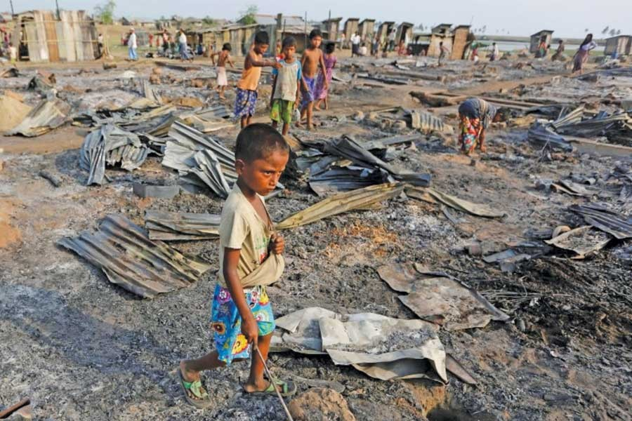 A boy walks among debris after fire destroyed shelters at a camp for internally displaced Rohingya Muslims in the western Rakhine State near Sittwe.  —Photo: Reuters