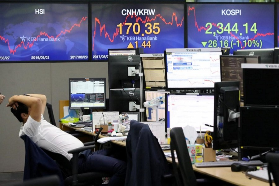 A currency dealer works in front of electronic boards showing the Korea Composite Stock Price Index (KOSPI) (R) at a dealing room of a bank in Seoul, South Korea August 29, 2017. Reuters