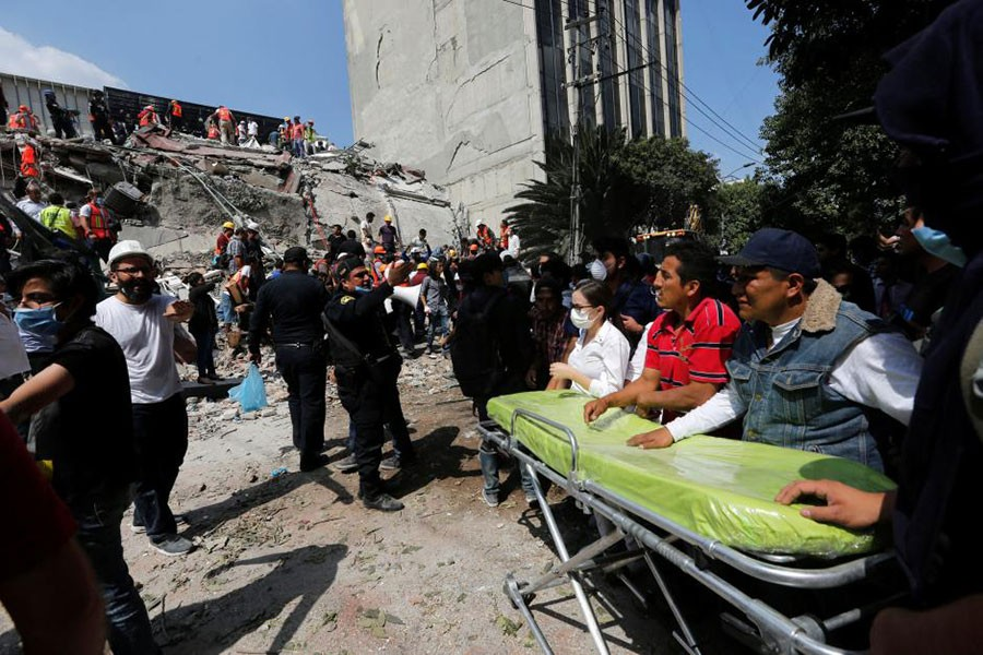 Paramedics wait as rescue personnel search for people in the rubble of a collapsed building after an earthquake hit Mexico City, Mexico on Tuesday. - Reuters photo
