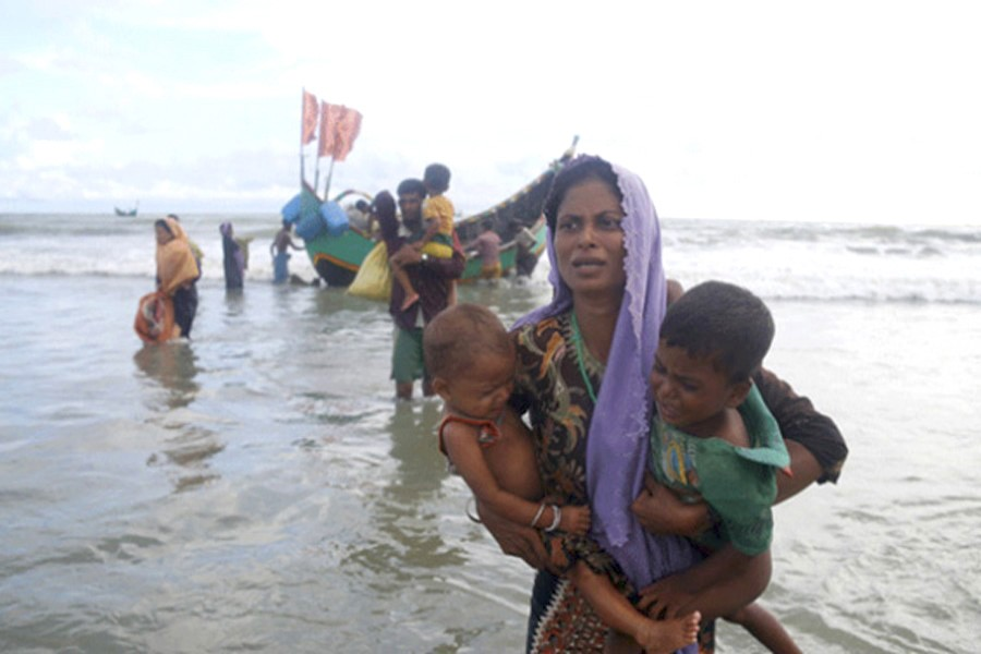 Rohingya people alight from a boat as they arrive at Shahparir Dip in Teknaf, Bangladesh. — IPS