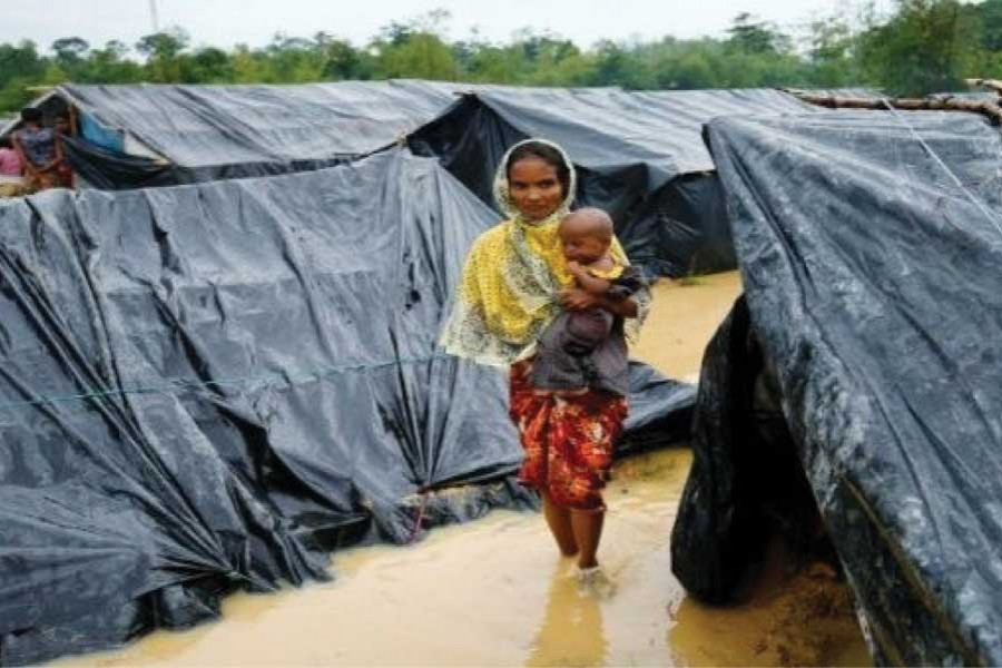 A Rohingya refugee woman and her child walk in floodwaters near makeshift shelters after heavy rains in Cox's Bazar in the second week of September, 2017.  —Photo: Reuters