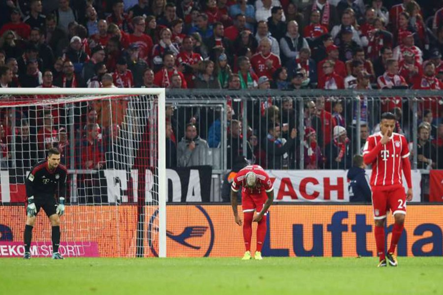 Bayern Munich players look dejected after Wolfsburg's Daniel Didavi scores their second goal. - Reuters photo