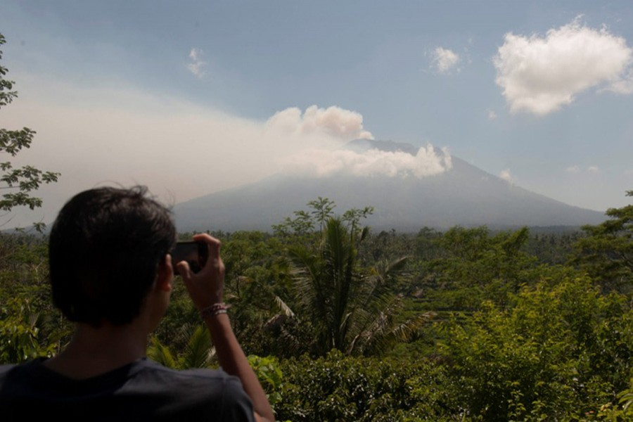 A local resident takes a picture of Mount Agung, an active volcano on Bali, Indonesia. - Reuters photo