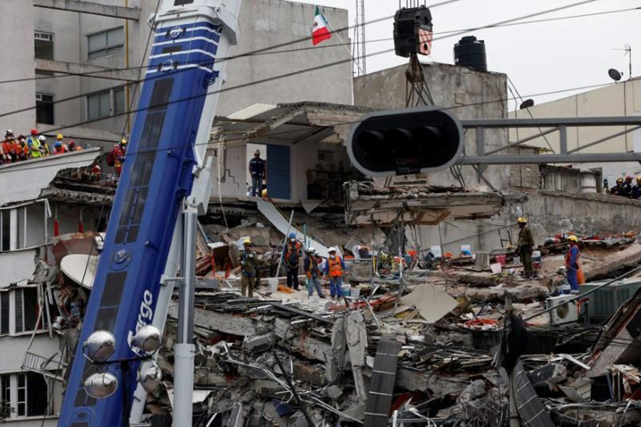 Rescue teams remove a platform as they search for survivors in a collapsed building after an earthquake at Roma neighborhood in Mexico City, Mexico on Saturday. - Reuters
