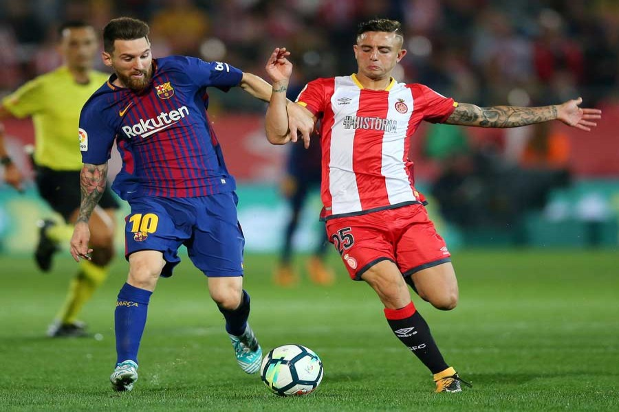 Barcelona's Lionel Messi in action with Girona's Pablo Maffeo during the Santander La Liga match between Girona and FC Barcelona at Estadi Montilivi stadium in Girona, Spain on Saturday. — Reuters