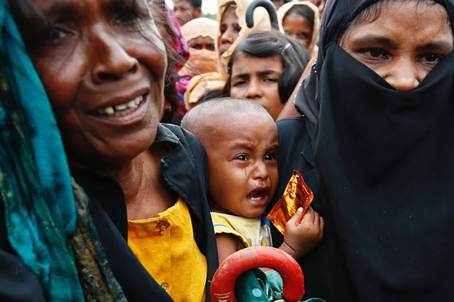 A Rohingya refugee baby cries as his mother jostles for aid in Cox's Bazar of Bangladesh on Sept 20, 2017.