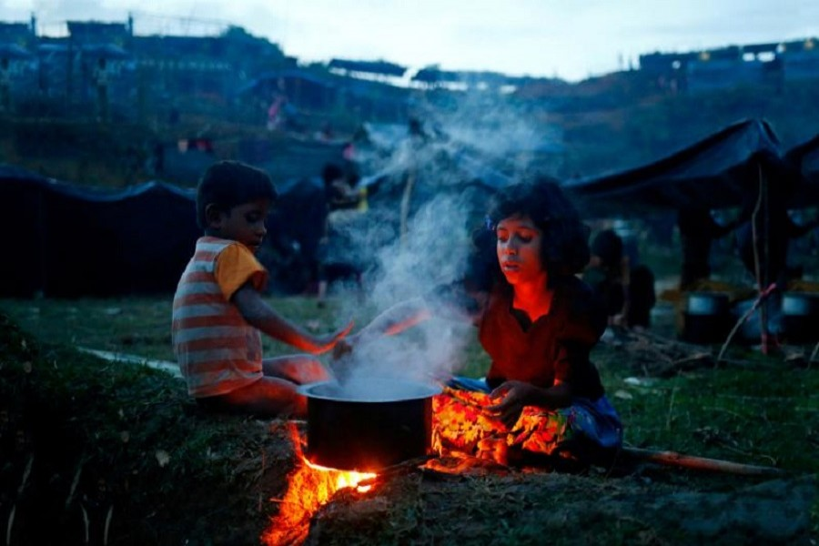 Rohingya refugee girl cooks a meal in an open place near Balukhali in Cox's Bazar, Bangladesh, Sept 4, 2017. Reuters