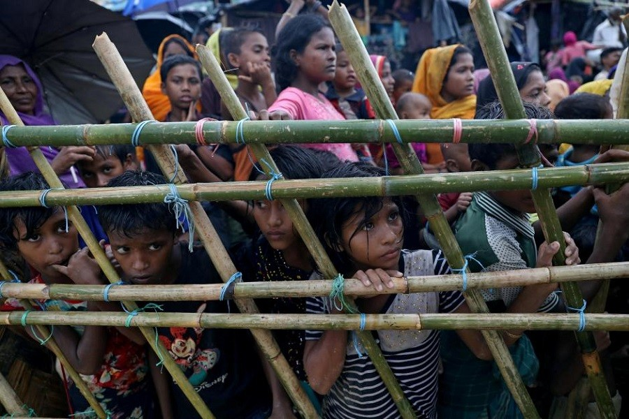 Rohingya refugees look through a fence as they wait outside of aid distribution premises at a refugee camp in Cox's Bazar, Bangladesh October 8, 2017. Reuters