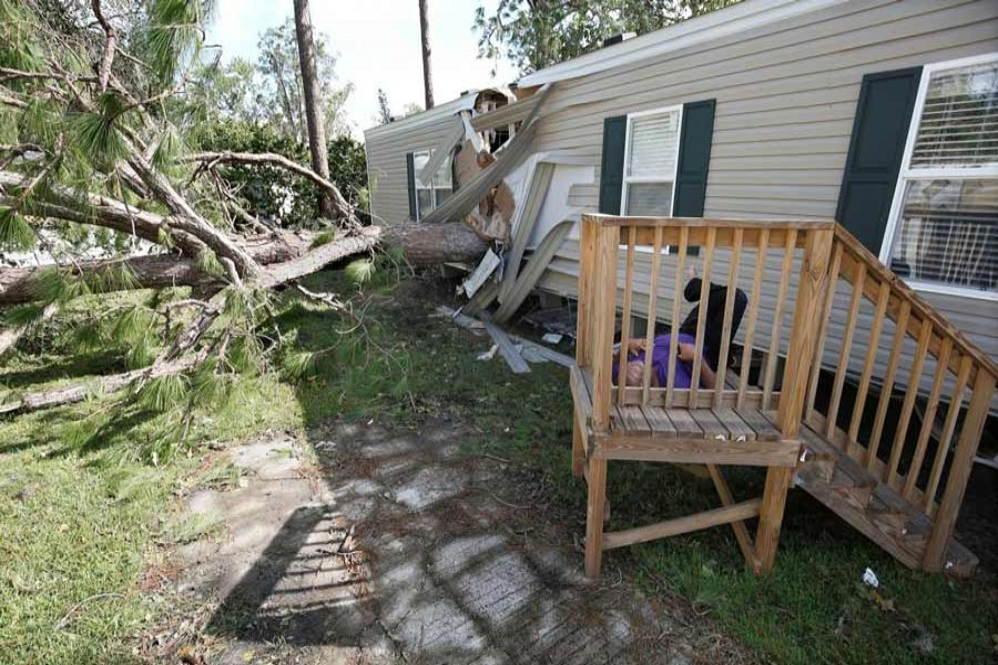 A resident of a mobile home park lies near a home that was destroyed by a falling tree in the wake of Hurricane Irma in Kissimmee, Florida, US September 12. — Reuters