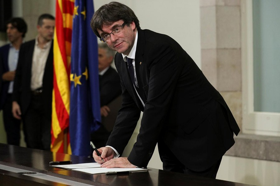 Catalan President Carles Puigdemont signs a declaration of independence at the Catalan regional parliament in Barcelona, Spain on Tuesday. - Reuters photo
