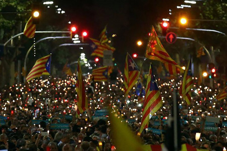 Protesters hold banners, candles and wave flags during a protest in Barcelona, Spain on Wednesday. - Reuters photo