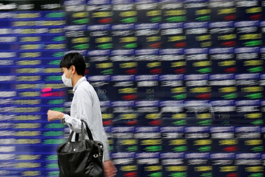 A man walks past an electronic stock quotation board outside a brokerage in Tokyo, Japan, September 22, 2017. Reuters/File Photo