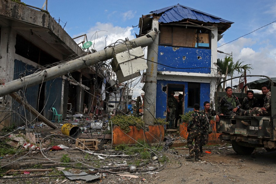 Soldiers stand guard in front of damaged buildings after government troops cleared the area from pro-Islamic State militant groups inside a war-torn area in Bangolo town of Marawi City, Philippines, on Monday. — Reuters
