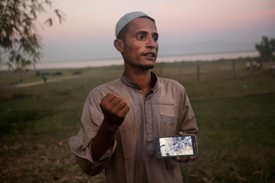 Osman Gani, a Rohingya man from Myanmar, shows a video clip that he shot on his mobile phone as he describes the violence standing on the bank of the Naf River. - AP file photo