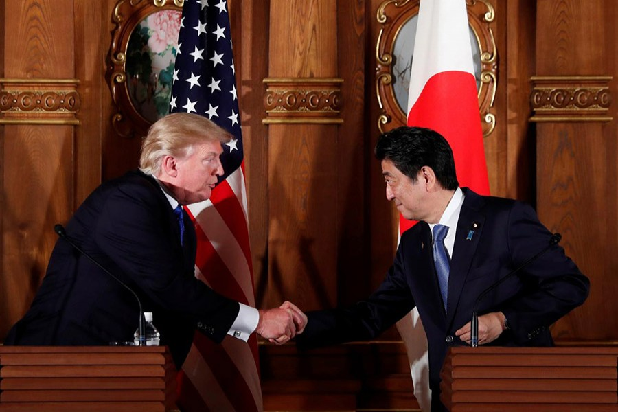 US President Donald Trump and Japan's Prime Minister Shinzo Abe shake hands during a news conference in Tokyo, Japan on Monday. - Reuters photo