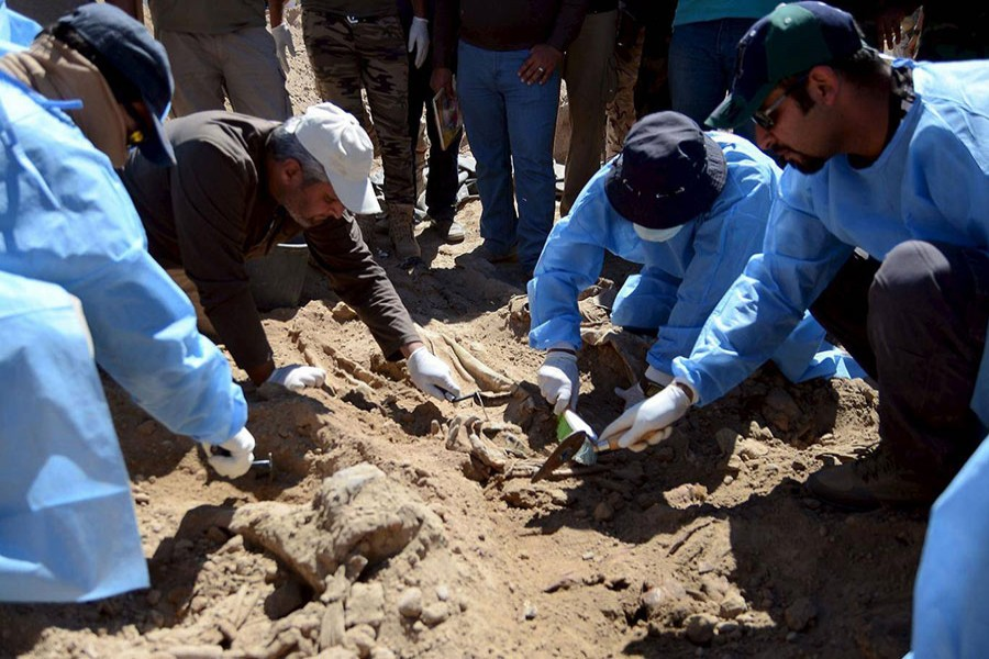 Members from the Iraqi forensic team search to extract the remains of the bodies. - Reuters file photo used for presentation.