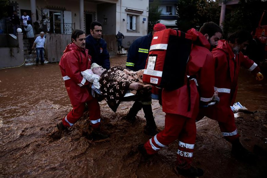 Hellenic Red Cross volunteers and firemen evacuate an elderly man following heavy rainfall in the town of Mandra. - Reuters photo