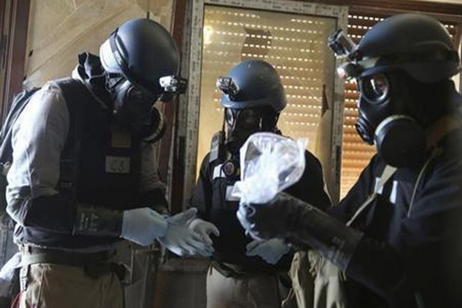 A UN chemical weapons expert, wearing a gas mask, holds a plastic bag containing samples from one of the sites of an alleged chemical weapons attack in the Ain Tarma neighbourhood of Damascus Aug 29, 2013. Reuters