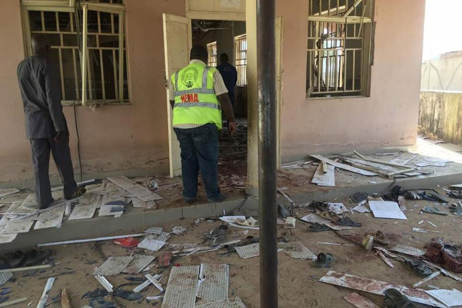 A National Emergency Management Agency (NEMA) staff inspects the damage at the site of a suicide bomber attack in Mubi in Adamawa state, in northeastern Nigeria on Tuesday. - Reuters