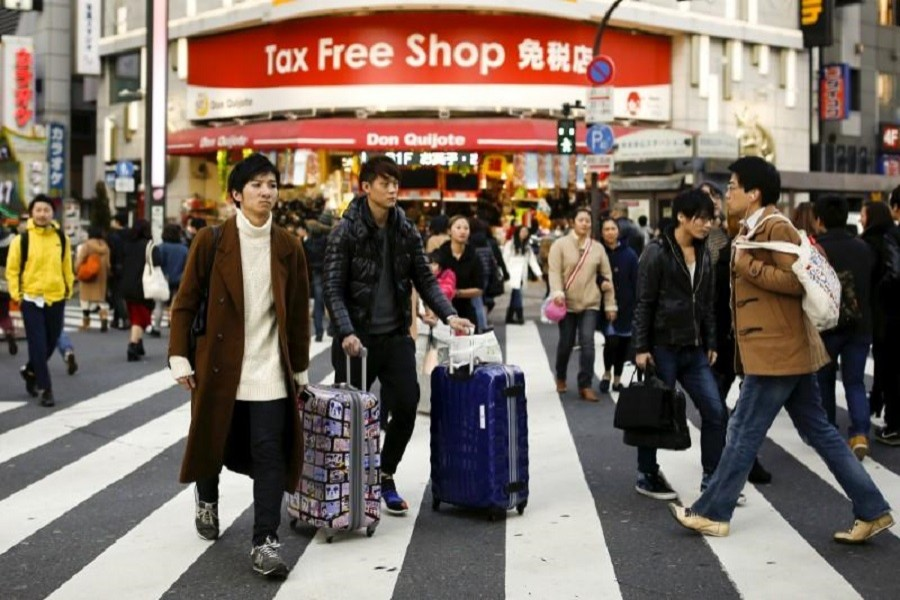 People cross a street outside a tax-free department store popular among Chinese tourists in Tokyo, Japan, February 11, 2016. Reuters/Files