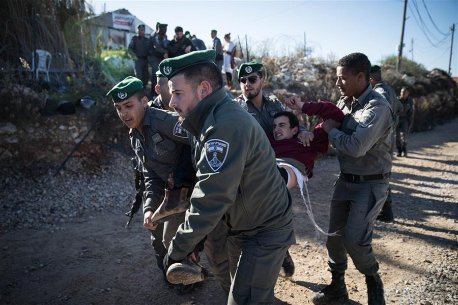 Israeli police scuffle with Jewish settlers during the evacuation of a building in Netiv Ha'avot, south of Jerusalem on Wednesday. - Xinhua photo