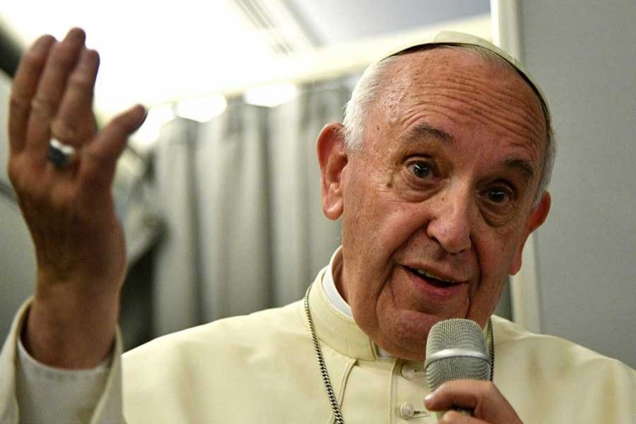 Pope Francis gestures during a news conference on board of the plane during his flight back from a trip to Myanmar and Bangladesh, December 2, 2017. Reuters