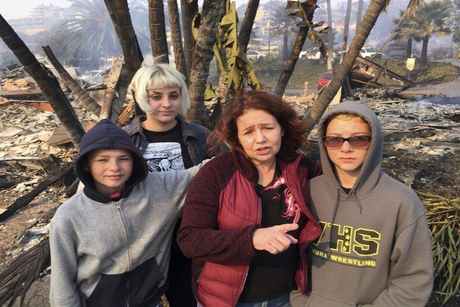 Lisa Kermode, second from right, and her children, from left, Damien, Lola and Michael, pose outside the ruins of their home after a wildfire swept through Ventura.Photo: AP