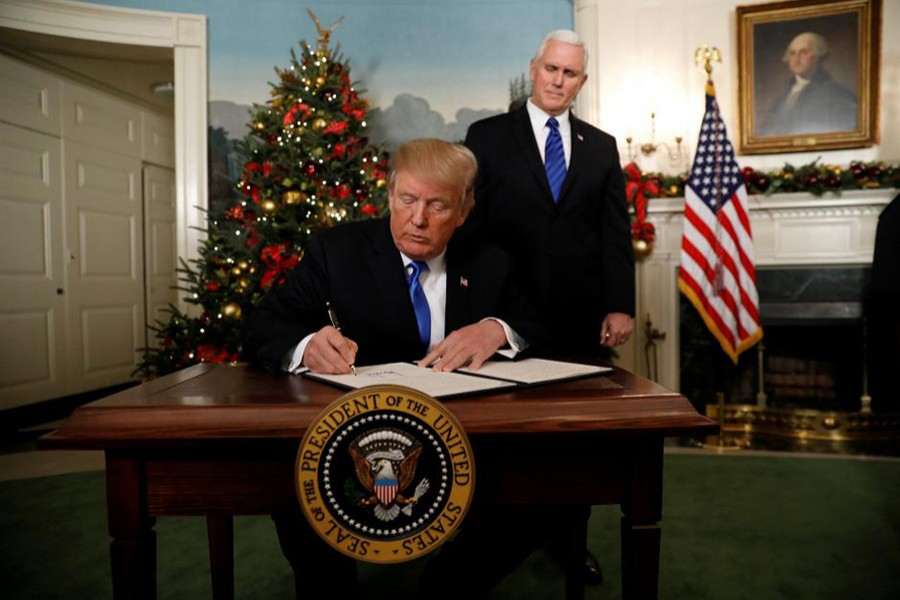 With Vice Pence Mike Pence looking on, U.S. President Donald Trump signs an executive order after he announced the U.S. would Jerusalem as the capital of Israel on Wednesday. - Reuters photo